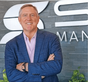 Bill Sowell standing in front of Sowell Management logo